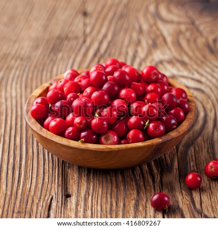 Cowberries, red bilberries, cranberries in a rustic bowl on a wooden background - stock photo