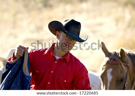 Cowboy and his horse out working - stock photo