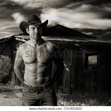 Cowboy at dusk in front of an old cabin in monochrome toned sepia - stock photo
