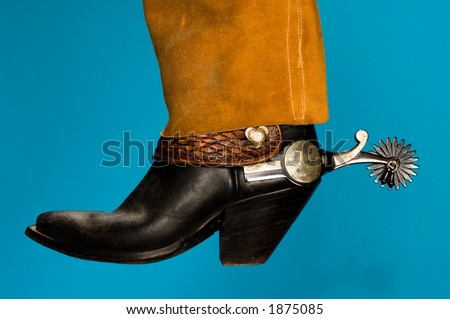 cowboy boot & spur with leather chaps - stock photo