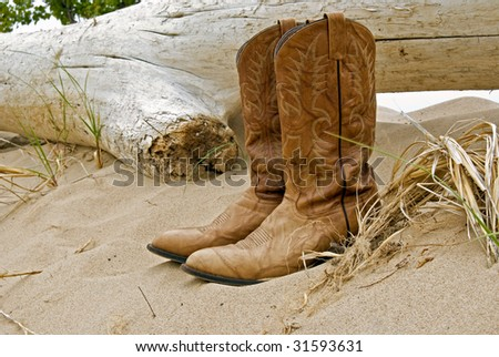 cowboy boots with driftwood - stock photo