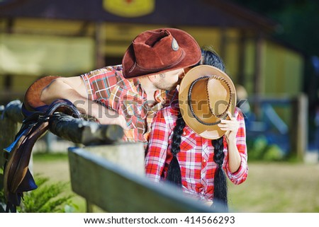 Cowboy couple kissing a guy and girl in cowboy hats. - stock photo
