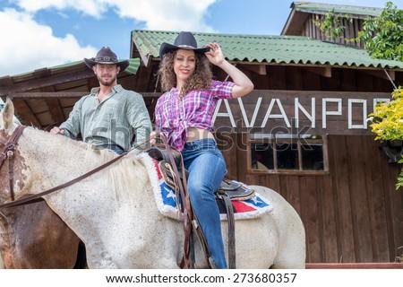 cowboy couple on horses - stock photo