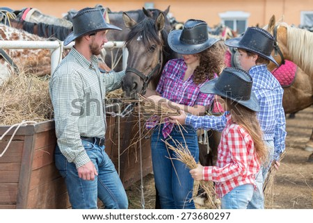 cowboy family of four feed the horses hay - stock photo