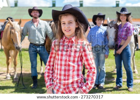 cowboy girl closeup portrait on background of her family with horses - stock photo