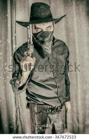 Cowboy Gunslinger Holding Gun Up to Hat. Cowboy Gunslinger holding his gun up to his hat Edited with a vintage film effect. - stock photo
