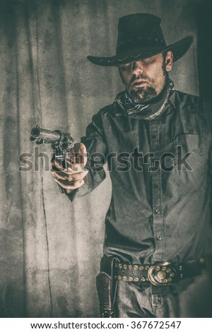 Cowboy Gunslinger Pointing Gun. Cowboy gunslinger aiming a classic colt 45 pistol off camera. Edited with a vintage film effect. (Focal point is the gun, NOT the cowboy) - stock photo