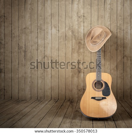 Cowboy hat and guitar against a wooden background. - stock photo