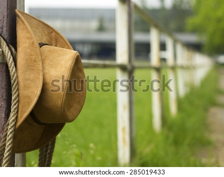 Cowboy hat and lasso on fence American Horse ranch background - stock photo