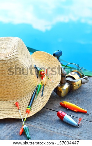Cowboy hat, fishing floats, fishing tackle in the nature - stock photo