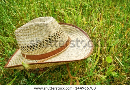 Cowboy hat on green grass - stock photo