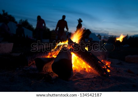 Cowboy hat  people talking next to the campfire light - stock photo