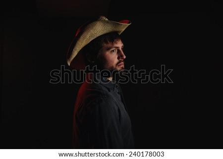 Cowboy in Studio Lighting body turned towards light variation - stock photo