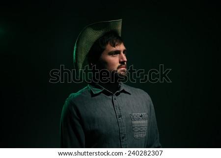 Cowboy in Studio Lighting serious face green rim light - stock photo