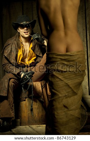 Cowboy looking at naced bondwoman against wooden background - stock photo