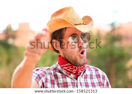 Cowboy man with sunglasses and cowboy hat pointing at camera saying WE WANT YOU. Male model in american rural western countryside landscape nature on ranch or farm, Utah, USA. - stock photo