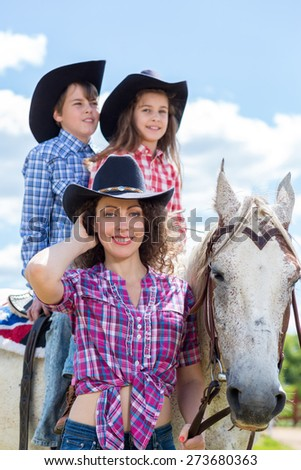 cowboy mother with son and daughter on a horse - stock photo
