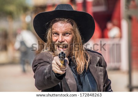 Cowboy Points Gun at You in Town - stock photo