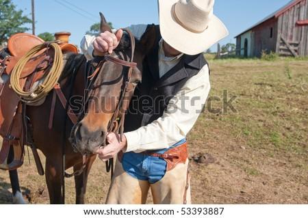 Cowboy preparing his horse to ride - stock photo