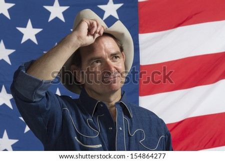 Cowboy tipping his hat in front of American flag, horizontal - stock photo
