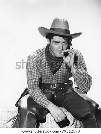 Cowboy with a cowboy hat smoking a cigarette - stock photo