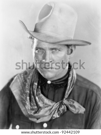 Cowboy with a hat looking sternly at the camera - stock photo