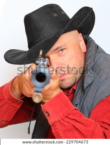 Cowboy with big bore rifle aimed at you. Legal defense and gun control concept.  - stock photo