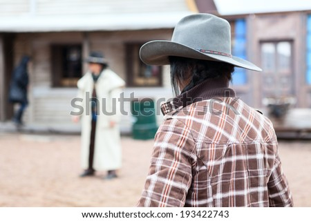 Cowboy with hat standing against another man in street - stock photo