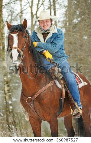 Cowboy with his horse. - stock photo