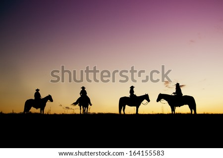 Cowboys and cowgirl silhouettes at sunset - stock photo