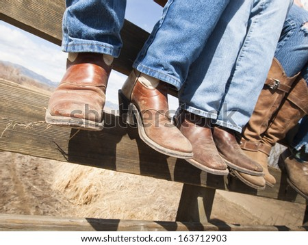 Cowboys and cowgirls sitting on wooden fence. - stock photo