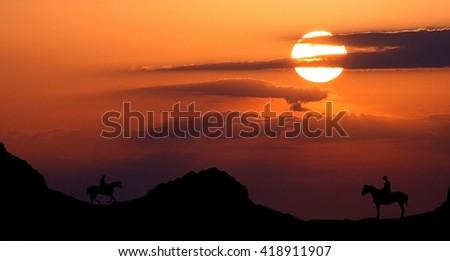 Cowboys riding at sunset - stock photo