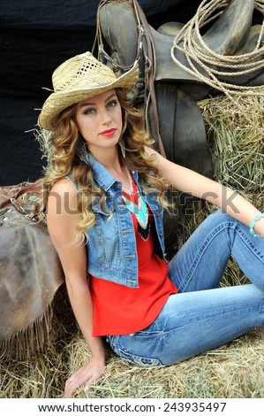 Cowgirl beauty expressions on hay stack outdoors. - stock photo