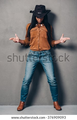 Cowgirl. Full length of beautiful young African woman in hat gesturing hand guns and looking down while standing against grey background - stock photo