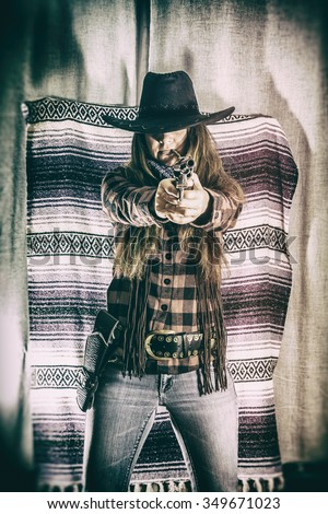 Cowgirl Gunslinger Standing and Aiming. Old west cowgirl gunslinger standing with peacemaker gun pointed just off camera, edited in vintage film style. - stock photo