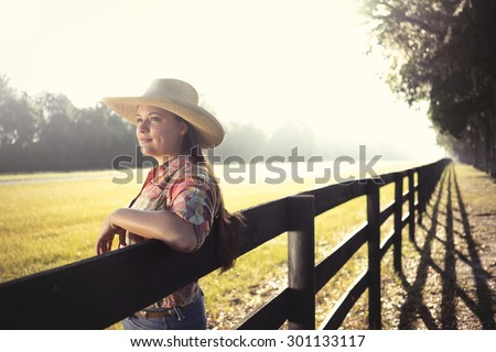 Cowgirl lady woman female wearing cowboy hat and flannel shirt with jeans leaning on country rural fence by a horse pasture paddock looking confident happy serene smart alone waiting watching patient - stock photo