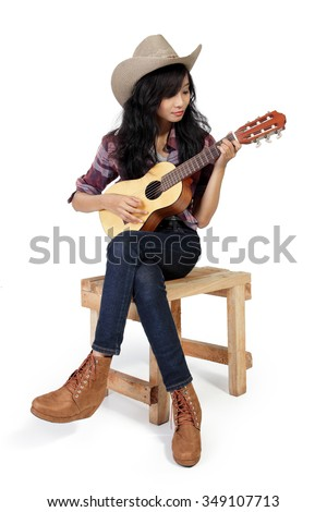 Cowgirl playing ukulele on a wooden chair, isolated on white background - stock photo