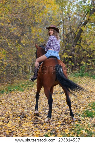 Cowgirl riding a bay horse in autumn woods - stock photo