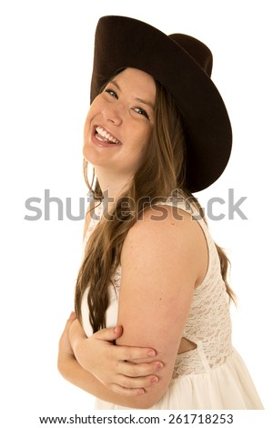 Cowgirl wearing a cowboy hat and a white sleeveless dress with her arms folded laughing - stock photo