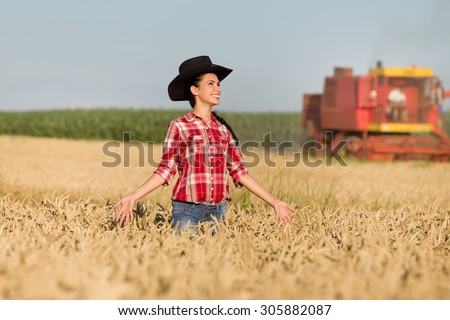 Cowgirl with plaid shirt and black hat walking in ripe wheat field during harvest - stock photo