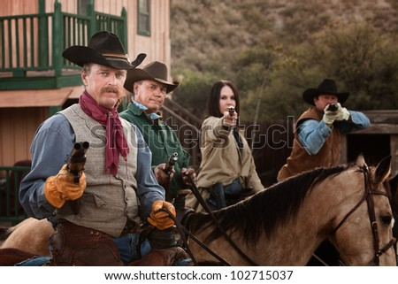 Cowgirl with three male companions in old American west scene - stock photo