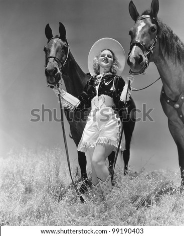 Cowgirl with two horses - stock photo