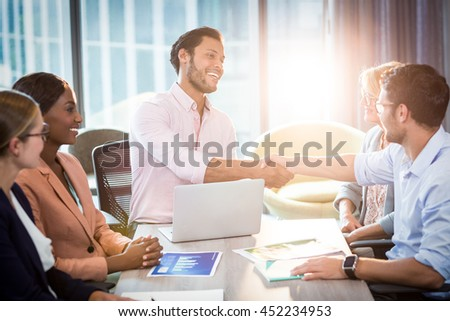 Coworker shaking hands with a colleague during a meeting in the office - stock photo