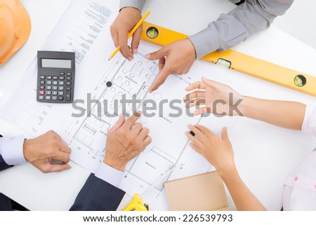 Coworkers discussing blueprint of the house - stock photo