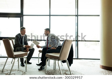 Coworkers discussing project in conference room - stock photo