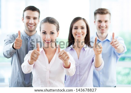 Coworkers showing thumbs up - stock photo