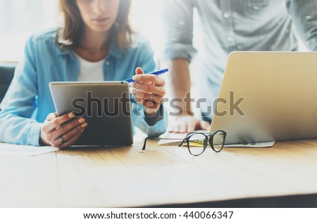 Coworkers team brainstorming process in modern office.Project producer reading report tablet,glasses wood table.Young business crew working with startup studio.Using Laptop. Blurred,film effect - stock photo