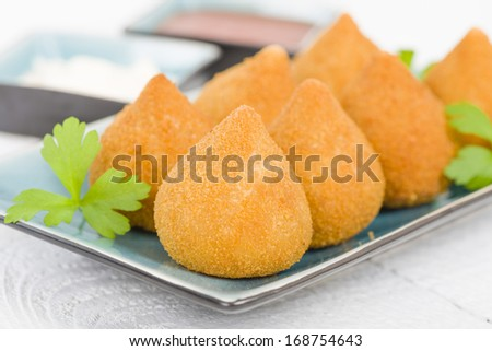 Coxinha de Galinha - Brazilian deep fried chicken snack, popular at local parties. Served with chili sauce and mayonnaise. - stock photo