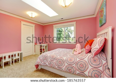 Cozy and gentle colors bedroom for girls. Pink walls blend with bedding. - stock photo
