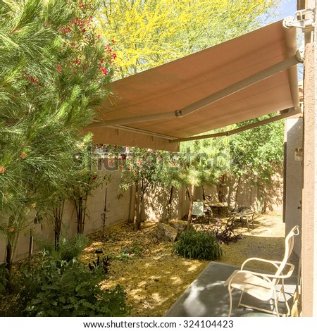 Cozy and shady automatic retractable awning for extra cooling, Arizona backyard - stock photo